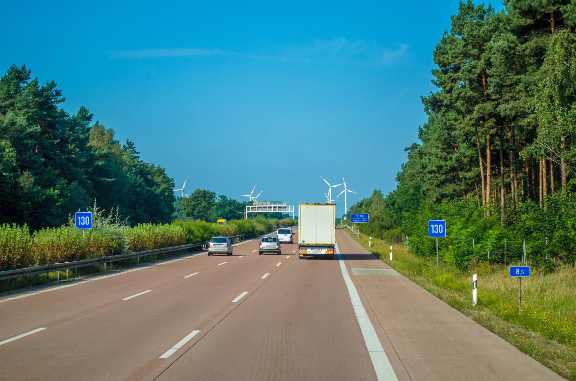 vehicle driving on freeway towards wind turbines
